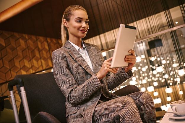Gelukkige jonge vrouw die digitale tablet gebruikt terwijl ze in het restaurant van het hotel zit