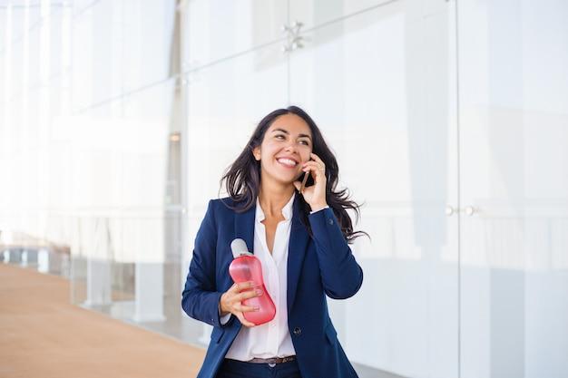 Gelukkige jonge vrouw die door celtelefoon spreekt