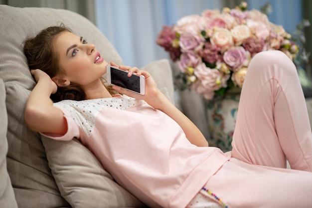 Gelukkige jonge vrouw die door slimme telefoon thuis spreekt. aantrekkelijke vrouw binnenshuis bellen.