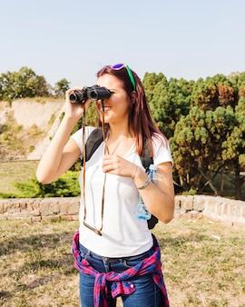Gelukkige jonge vrouw die door verrekijkers in openlucht kijkt