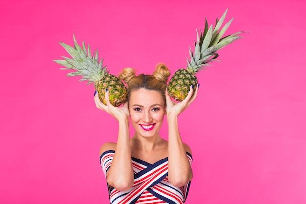 Gelukkige jonge vrouw die een ananas op een roze muur houdt.