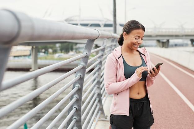 Gelukkige jonge vrouw die een bericht sms't op haar mobiele telefoon terwijl ze in het stadion rent