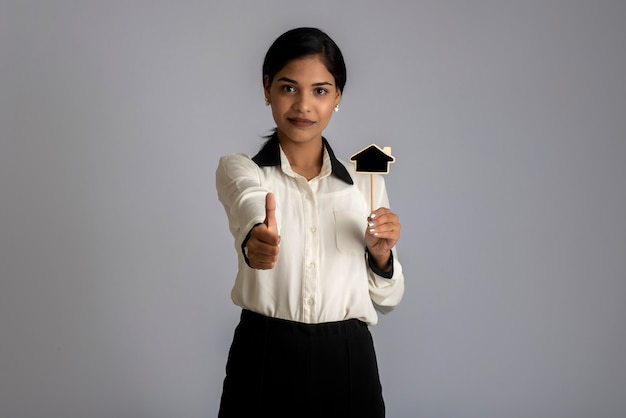Gelukkige jonge vrouw die een bord van het huisknipsel in haar handen op een grijze muur houdt.