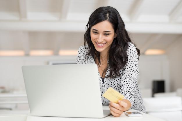 Gelukkige jonge vrouw die een creditcard houdt en thuis online winkelt