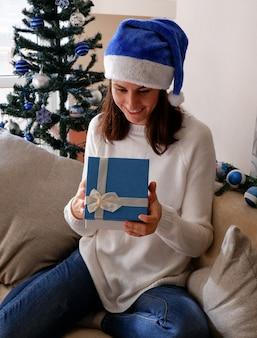 Gelukkige jonge vrouw die een kerstcadeaudoos opent