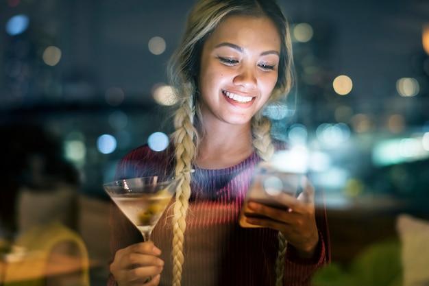 Gelukkige jonge vrouw die een smartphone gebruiken bij een dakbar in de avond
