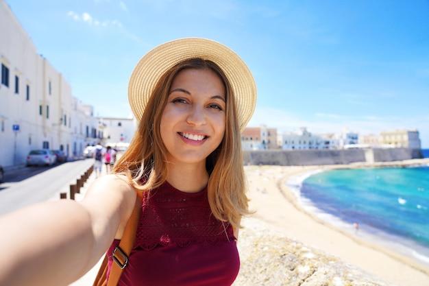 Gelukkige jonge vrouw die een zelffoto maakt met een smartphone die momenten vastlegt tijdens de zomervakantie
