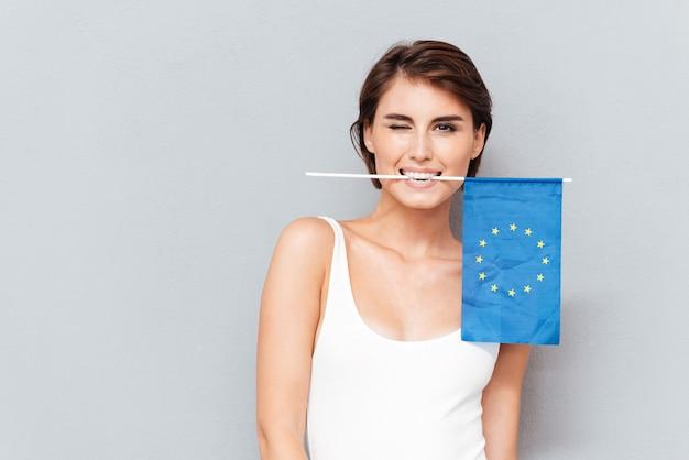 Gelukkige jonge vrouw die europese vlag in tanden houdt en over grijze achtergrond knipoogt