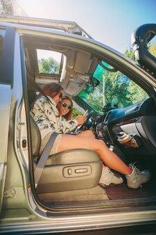 Gelukkige jonge vrouw die foto in een smartphone toont aan haar vriend in de auto. vrouwelijke vriendschap en vrije tijd concept.