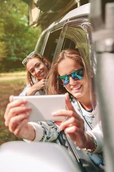 Gelukkige jonge vrouw die foto's maakt met een smartphone naar haar vriend die achterover leunt door de raamauto in een roadtrip-avontuur. vrouwelijke vriendschap en vrije tijd concept.