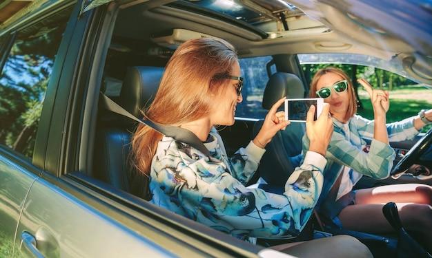 Gelukkige jonge vrouw die foto's maakt met een smartphone naar haar vriend die het overwinningsteken in de auto laat zien. vrouwelijke vriendschap en vrije tijd concept.