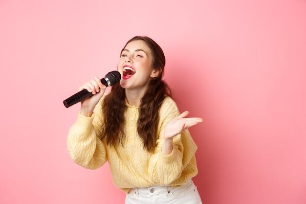 Gelukkige jonge vrouw die geniet van het spelen van karaoke, zingen in mic, opzij kijken naar scherm met teksten, vrolijk glimlachend, staande tegen roze muur.