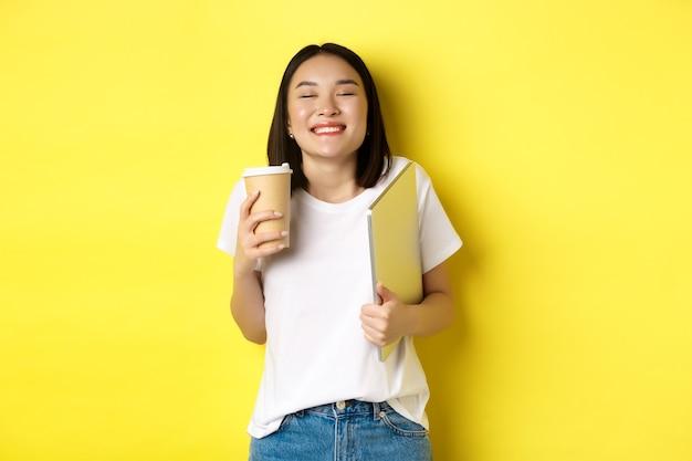 Gelukkige jonge vrouw die geniet van koffie uit café en glimlacht, kopje en laptop vasthoudt, staande over gele achtergrond