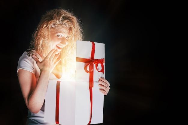 Gelukkige jonge vrouw die geschenkdoos opent. geïsoleerd op zwarte achtergrond