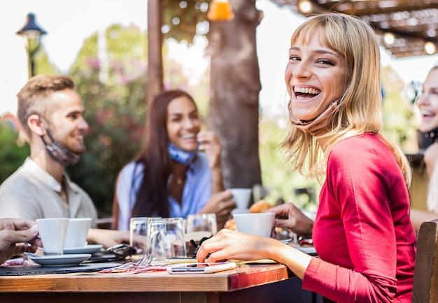 Gelukkige jonge vrouw die gezichtsmasker draagt bij het restaurant. groep vrienden die koffie drinken die aan de bar zitten.