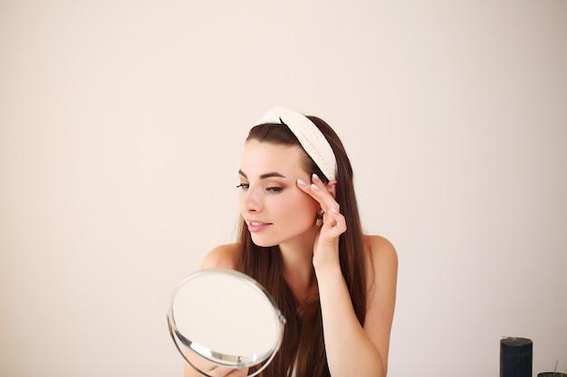 Gelukkige jonge vrouw die gezichtsroom zet om de zorg van de ochtend gezonde huid te doen.