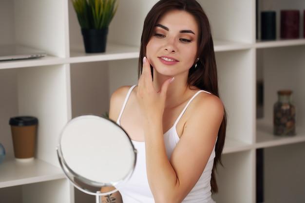 Gelukkige jonge vrouw die gezichtsroom zet om de zorg van de ochtend gezonde huid te doen