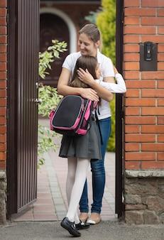 Gelukkige jonge vrouw die haar dochter na school voor het huis knuffelt