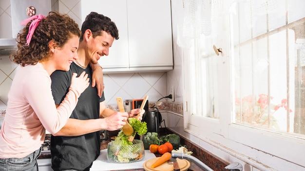 Gelukkige jonge vrouw die haar echtgenoot van achter het voorbereidingen treffen van salade in de kom omhelzen
