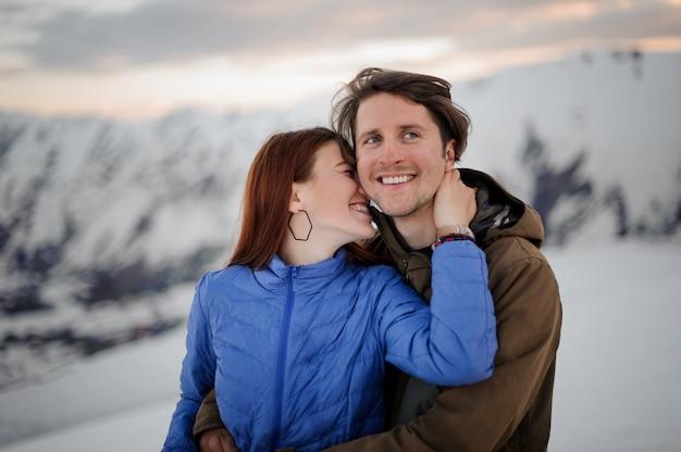 Gelukkige jonge vrouw die haar glimlachende vriend in bergen kust