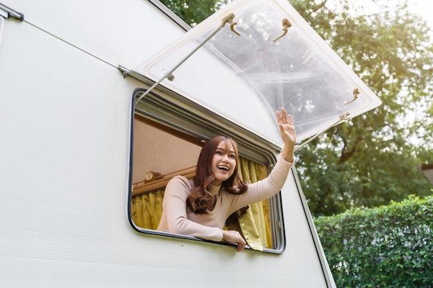 Gelukkige jonge vrouw die haar hand opheft bij raam van een camper rv van camper