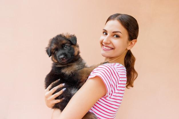 Gelukkige jonge vrouw die haar huisdierenpuppy op oranje achtergrond houdt