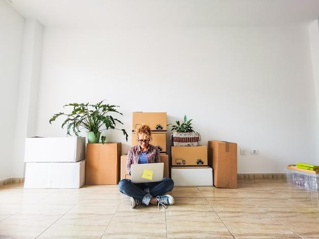Gelukkige jonge vrouw die haar laptop thuis op de vloer gebruikt met de dozen en pakken op haar rug