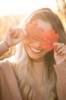 Gelukkige jonge vrouw die haar ogen met esdoornblad in openlucht verbergen bij