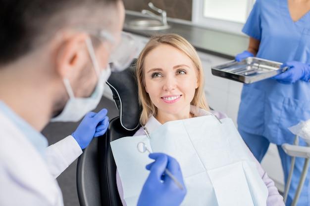 Gelukkige jonge vrouw die haar tandarts met brede glimlach bekijkt terwijl hij vóór mondeling onderzoek zit