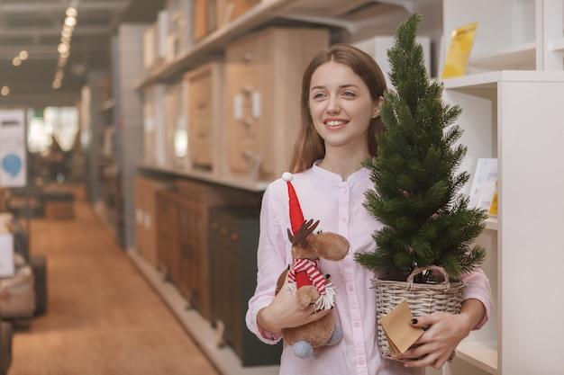 Gelukkige jonge vrouw die het huisdecoraties van kerstmis kopen bij meubilairopslag