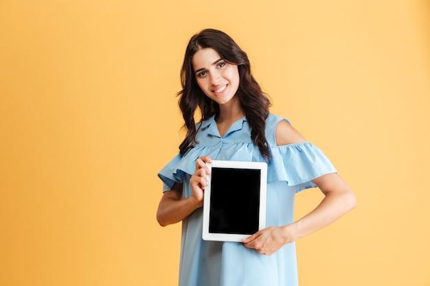 Gelukkige jonge vrouw die het lege geïsoleerde scherm van de tabletcomputer toont