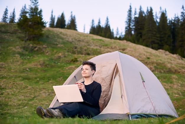 Gelukkige jonge vrouw die het uitzicht bewondert terwijl het zitten in haar tent in de bergen en het werken aan laptop