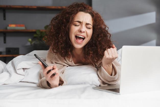 Gelukkige jonge vrouw die huiskleren draagt met behulp van laptop en smartphone terwijl ze thuis in bed op wit linnen ligt