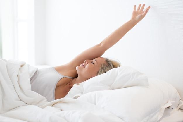 Gelukkige jonge vrouw die in bed na slaap uitrekt