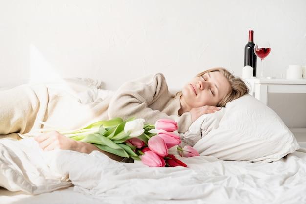Gelukkige jonge vrouw die in het bed ligt dat pyjama's draagt die het boeket van tulpbloemen houden
