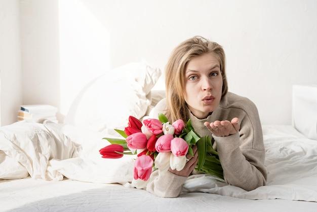 Gelukkige jonge vrouw die in het bed ligt dat pyjama's draagt die het boeket van tulpbloemen houdt en een kus blaast