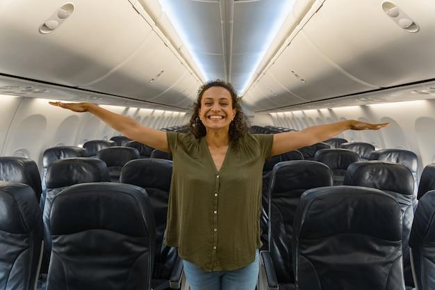 Gelukkige jonge vrouw die in het gangpad staat in het vliegtuig