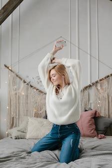 Gelukkige jonge vrouw die in hoofdtelefoons aan muziek van smartphone luisteren en thuis op bed dansen