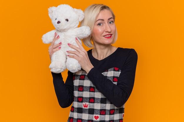 Gelukkige jonge vrouw die in mooie kleding teddybeer als gift houden die voorzijde glimlachen die vrolijk de dag van internationale vrouwen vieren die zich over groene muur bevinden