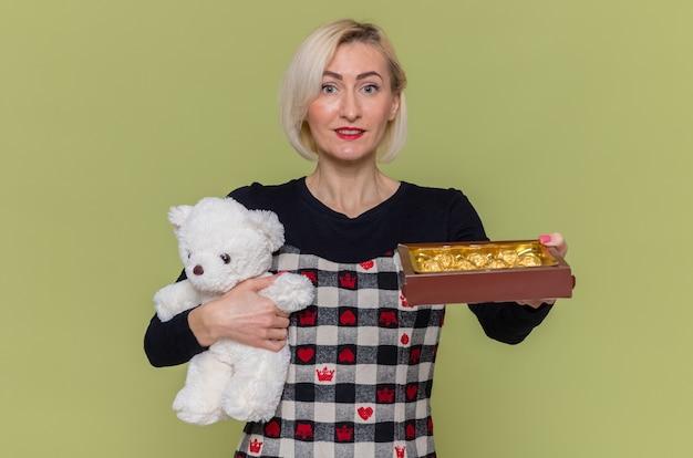 Gelukkige jonge vrouw die in mooie kleding teddybeer en chocoladesuikergoed houdt als giften glimlachend vrolijk viert de dag van de internationale vrouw die zich over groene muur bevindt