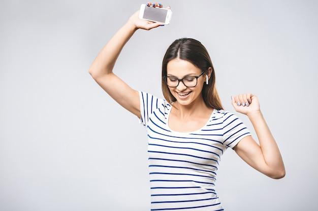 Gelukkige jonge vrouw die in oortelefoons aan muziek met slimme telefoon luistert