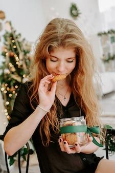 Gelukkige jonge vrouw die kerstkoekjes in de keuken eet en glimlacht