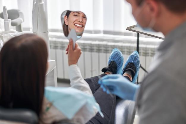 Gelukkige jonge vrouw die lacht en haar perfecte gezonde tanden in de spiegel bekijkt, op het kantoor van de tandarts.