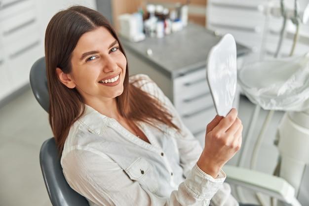 Gelukkige jonge vrouw die lacht en haar perfecte gezonde tanden in de spiegel bekijkt, zittend in een tandartsstoel op het tandartskantoor.