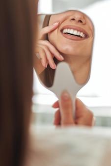 Gelukkige jonge vrouw die lacht en haar perfecte gezonde tanden in de spiegel van dichtbij bekijkt, op het kantoor van de tandarts.