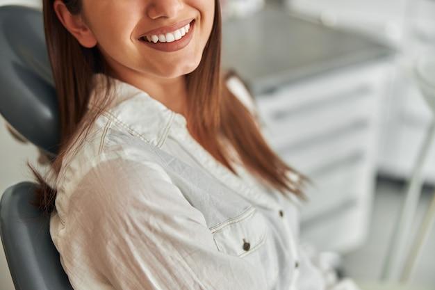 Gelukkige jonge vrouw die lacht en haar perfecte gezonde tanden van dichtbij bekijkt, op het kantoor van de tandarts.
