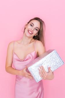Gelukkige jonge vrouw die lacht op een geïsoleerde roze achtergrond terwijl ze het vieringsconcept van de geschenkdoos vasthoudt