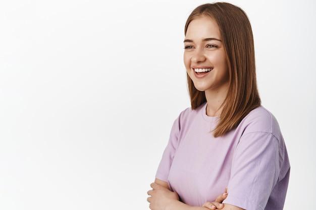 Gelukkige jonge vrouw die lacht, vrolijk glimlacht, wegkijkt naar de linkerkant voor uw promotietekst, advertentie, in een t-shirt tegen een witte muur staat.