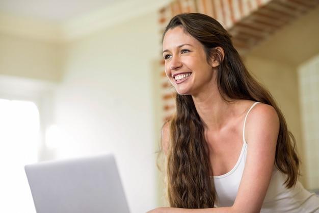 Gelukkige jonge vrouw die laptop in keuken met behulp van