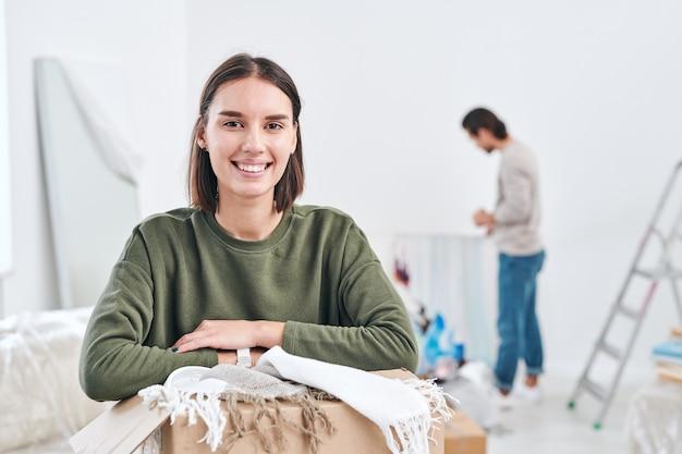 Gelukkige jonge vrouw die met brede glimlach naar u kijkt tijdens het uitpakken van dozen